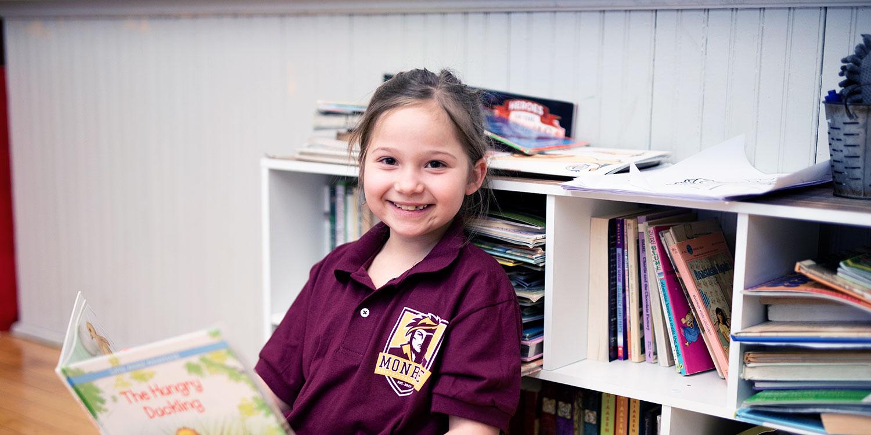 Elementary student reading in front of bookshelf.