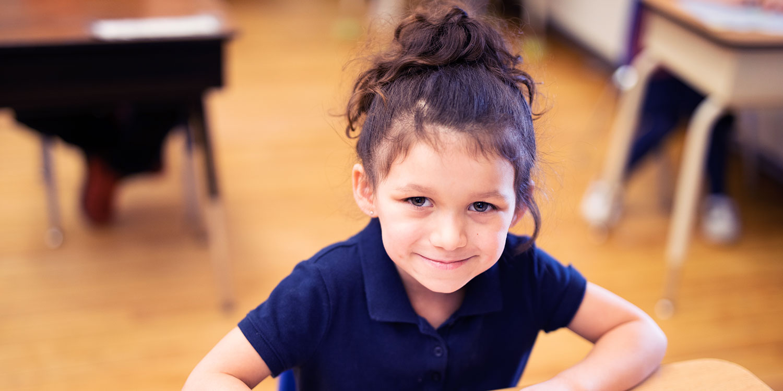 Smiling student sitting at desk.