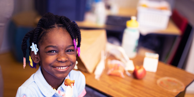 Smiling student eating at desk.