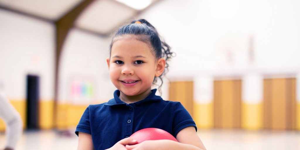 Smiling student holding ball in school gym.