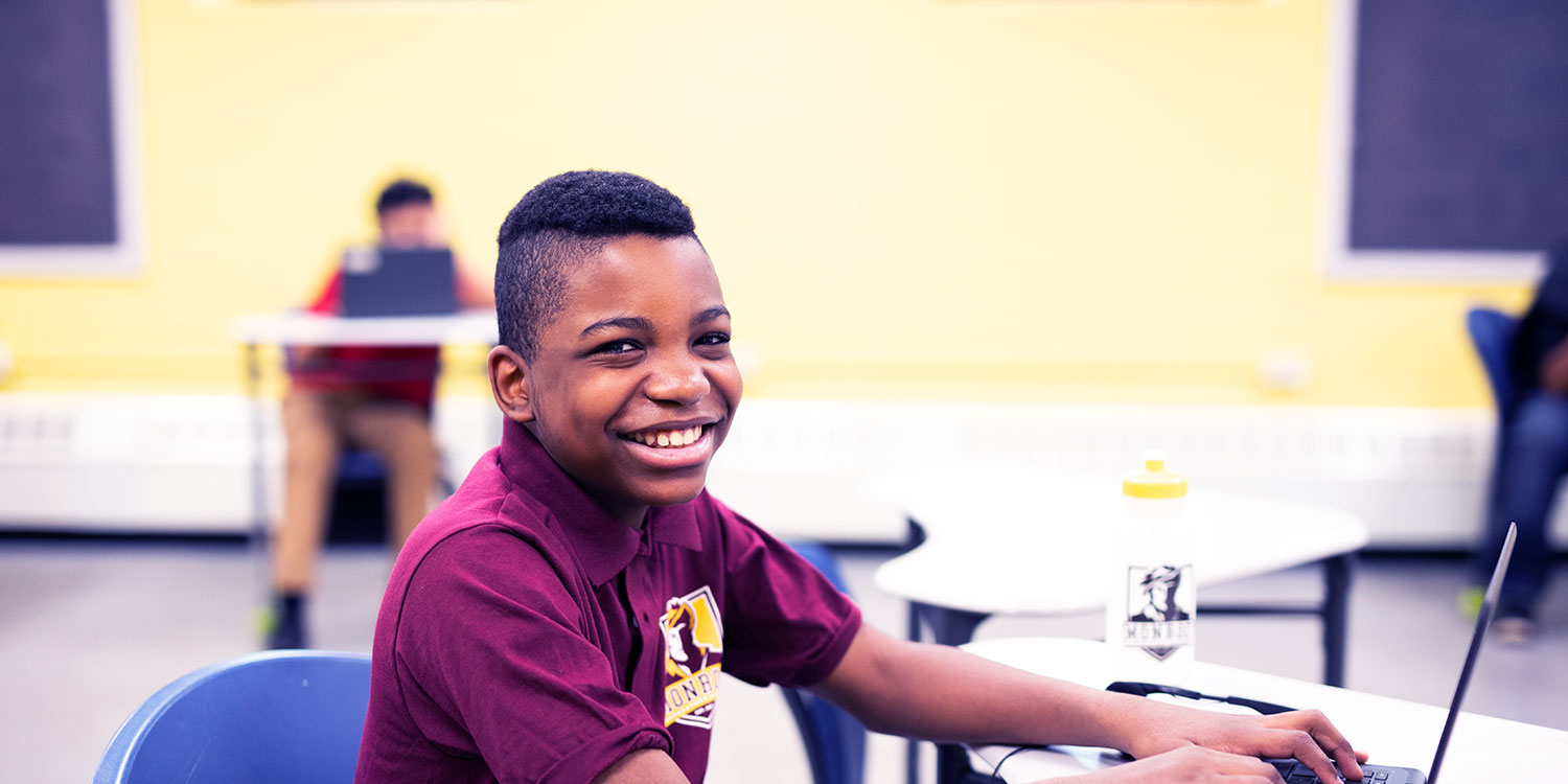 Smiling student working on laptop at desk.