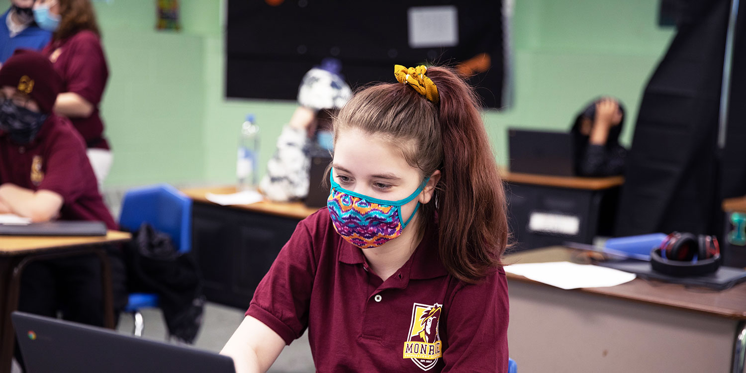 Masked middle school student working on laptop at desk.